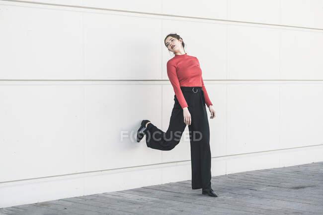 Elegante giovane donna appoggiata a un muro — Foto stock