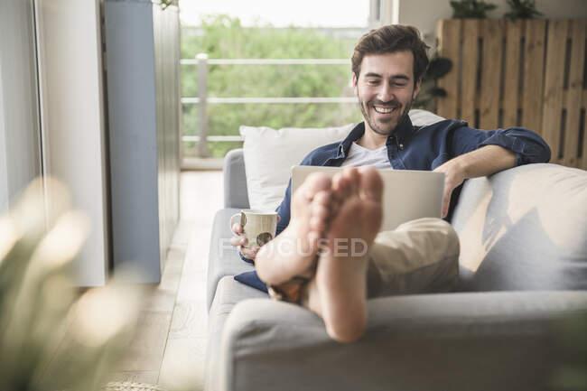 Jung auf der Couch sitzen, Laptop benutzen, Kaffee trinken — Stockfoto