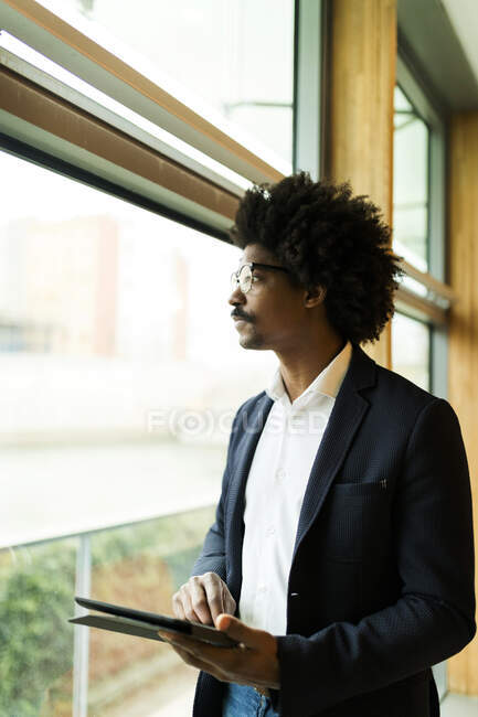 Businessman standing at the window using tablet — Stock Photo