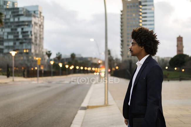 Spagna, Barcellona, uomo d'affari in piedi in una strada della città al tramonto — Foto stock