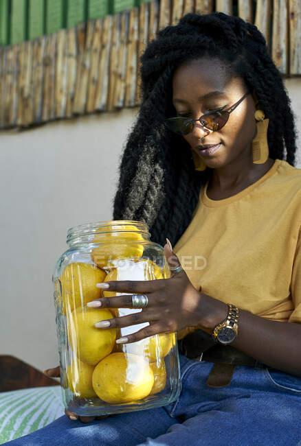 Молодая женщина с дредами держит банку, полную лимонов — Stock Photo