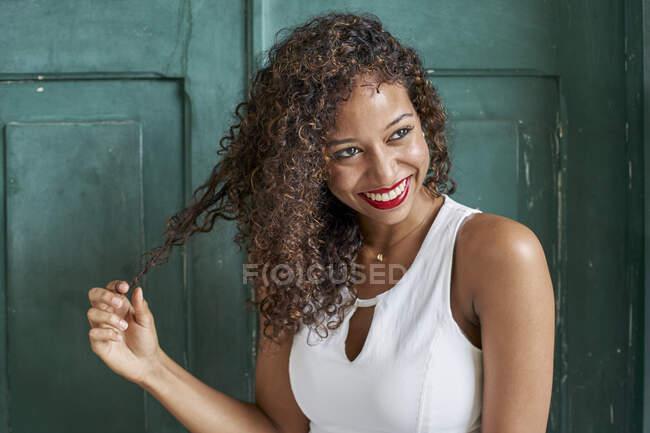 Retrato de jovem sorridente com cabelo encaracolado na frente da porta de madeira verde — Fotografia de Stock