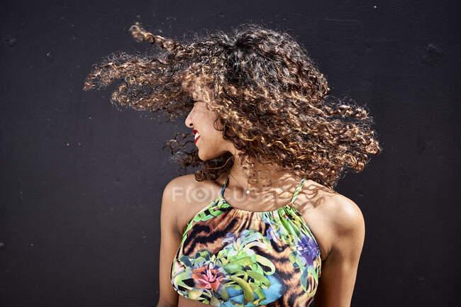 Sorrindo jovem mulher jogando seu cabelo encaracolado na frente de fundo escuro — Fotografia de Stock
