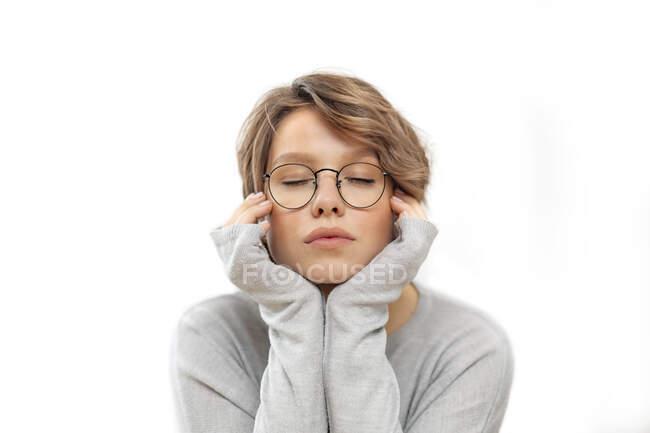 Retrato de mujer joven con gafas y ojos cerrados - foto de stock