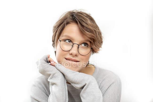 Retrato de una joven pensante con gafas y auriculares inalámbricos - foto de stock