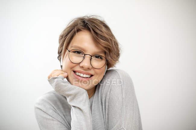 Retrato de mujer joven riendo con auriculares inalámbricos y gafas - foto de stock