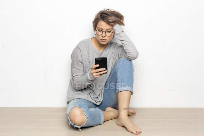 Retrato de mujer joven con auriculares inalámbricos sentada en el suelo mirando el teléfono celular - foto de stock
