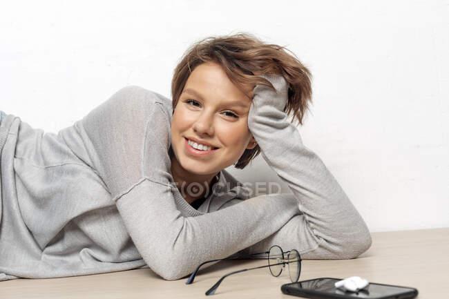 Retrato de una joven sonriente tirada en el suelo - foto de stock