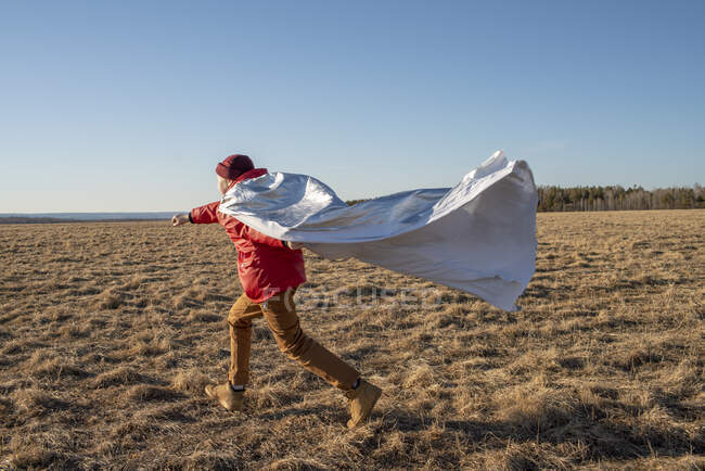 Ragazzo vestito da supereroe che corre nel paesaggio della steppa — Foto stock