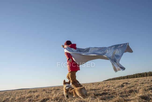 Ragazzo vestito da supereroe che corre con il cane nel paesaggio della steppa — Foto stock