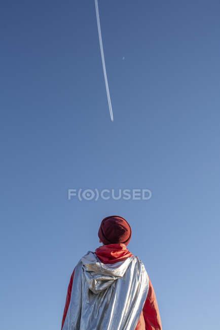 Vista posteriore del ragazzo travestito da supereroe guardando le tracce di vapore nel cielo — Foto stock