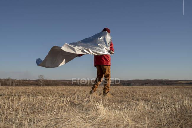 Vista posteriore del ragazzo travestito da supereroe in piedi nel paesaggio della steppa — Foto stock