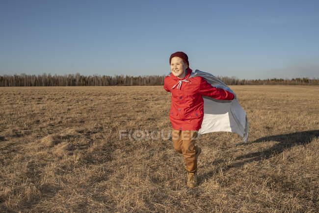 Ragazzo felice vestito da supereroe che corre nel paesaggio della steppa — Foto stock