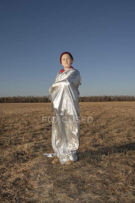 Ragazzo avvolto in costume da supereroe in piedi nel paesaggio steppico — Foto stock