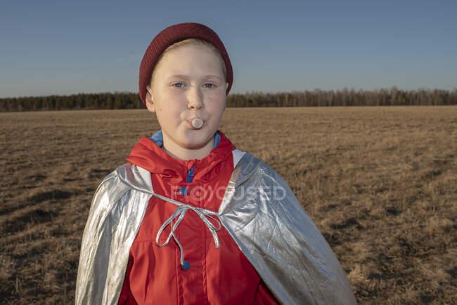 Ritratto di ragazzo travestito da supereroe nel paesaggio della steppa che soffia una bolla di gomma da masticare — Foto stock