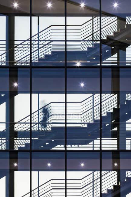Una persona subiendo escaleras en un edificio de oficinas - foto de stock
