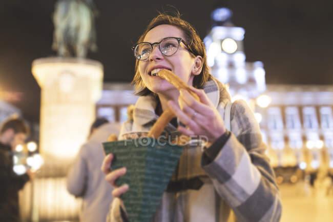 España, Madrid, joven en la ciudad por la noche comiendo churros típicos con chocolate - foto de stock