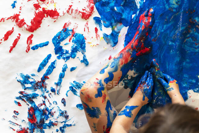 Toddler girl sitting on paper on the floor playing with finger paint, partial view — Stock Photo