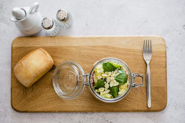 Скло салату з огірками, курячим горохом, цибулею, вишневими помідорами, базилем, насінням чії та нарізаними мигдалями. — стокове фото