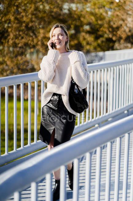 Giovane donna sorridente al telefono che cammina in passerella in autunno — Foto stock