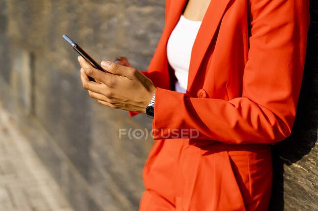 Woman wearing fashionable red pantsuit holding cell phone, partial view — Stock Photo