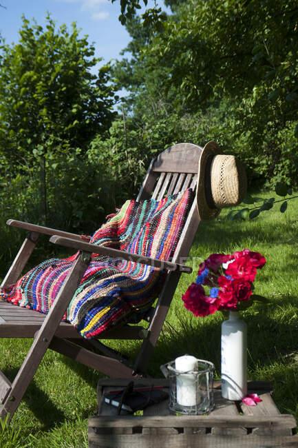 Cojín hecho de alfombra patchwork en la tumbona en el jardín - foto de stock