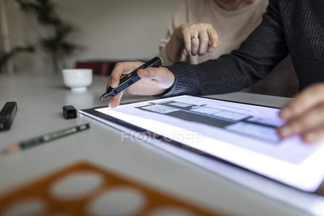 Close-up of man using tablet with architectural plan — Stock Photo
