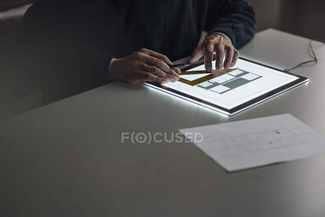 Close-up of senior man using tablet with architectural plan — Stock Photo