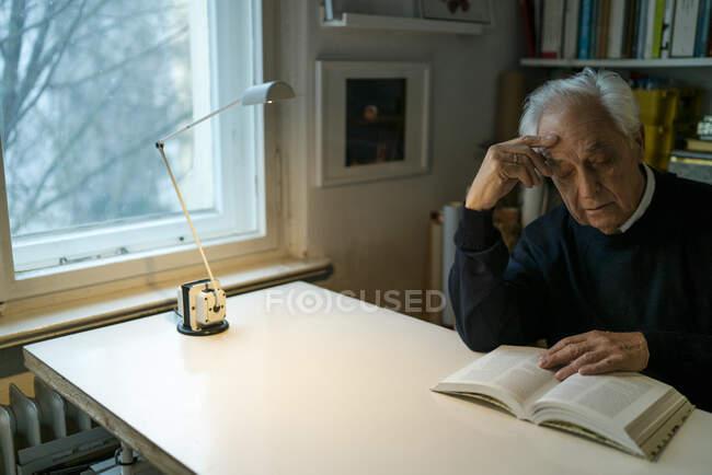 Hombre mayor leyendo libro en casa - foto de stock