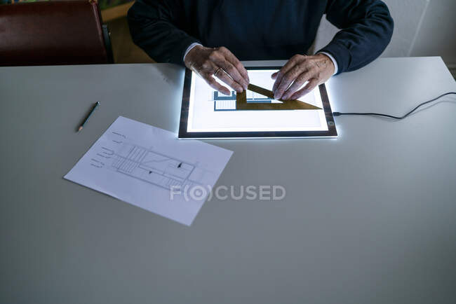 Close-up of senior man using ruler and tablet with architectural plan — Stock Photo