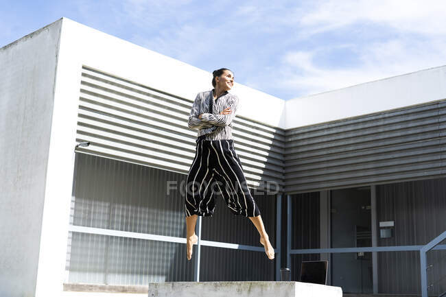 Female ballet dancer jumping on a bench in front of an office building — Stock Photo