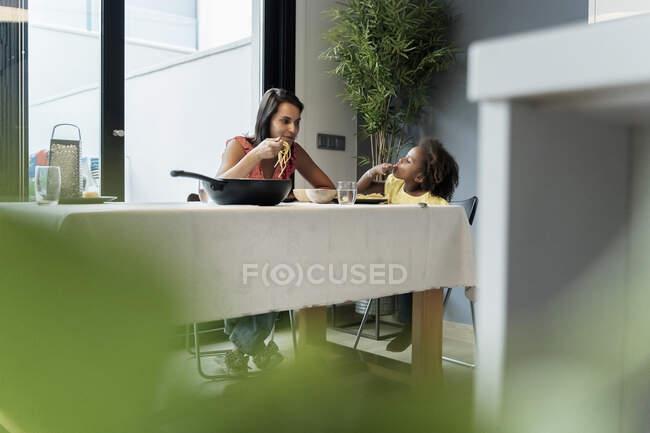 Мама з донькою їдять макарони за обіднім столом. — стокове фото