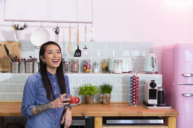 Mulher feliz com uma bebida na cozinha do escritório — Fotografia de Stock