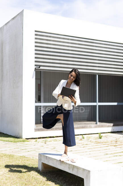 Female ballet dancer using tablet in front of an office during work, standing on one leg — Stock Photo