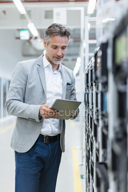 Empresario con tableta examinando una máquina en una fábrica moderna - foto de stock