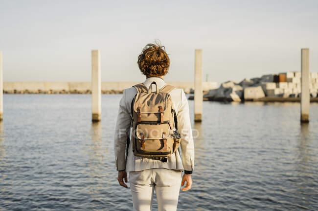 Vista trasera del hombre de negocios con mochila mirando a la distancia, Barcelona, España - foto de stock