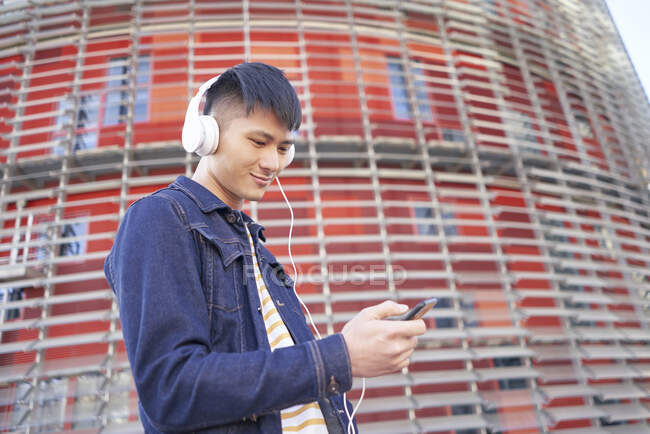 Portrait of smiling young man with headphones looking at cell phone, Barcelona, Spain - foto de stock