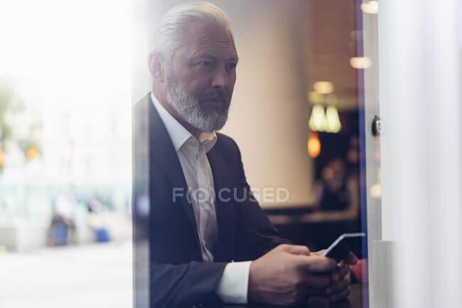 Зрілий бізнесмен з мобільним телефоном у кафе. — стокове фото