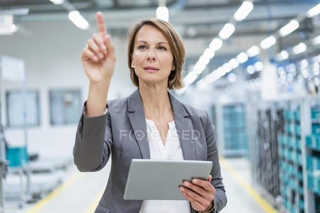 Зайнята жінка з планшетом на сучасному заводі торкається віртуального екрану — стокове фото