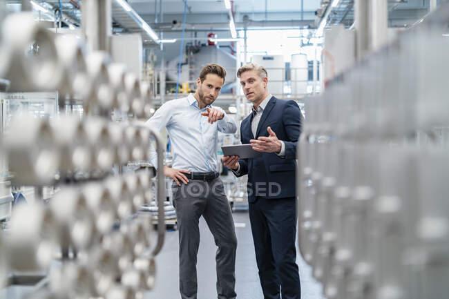 Два бізнесмени з планшетом, які розмовляють на сучасній фабриці. — стокове фото