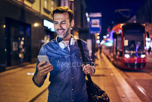 Smiling man using his smartphone in the city at night — Stock Photo