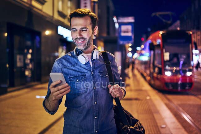 Усміхнений чоловік вночі користується своїм смартфоном. — стокове фото