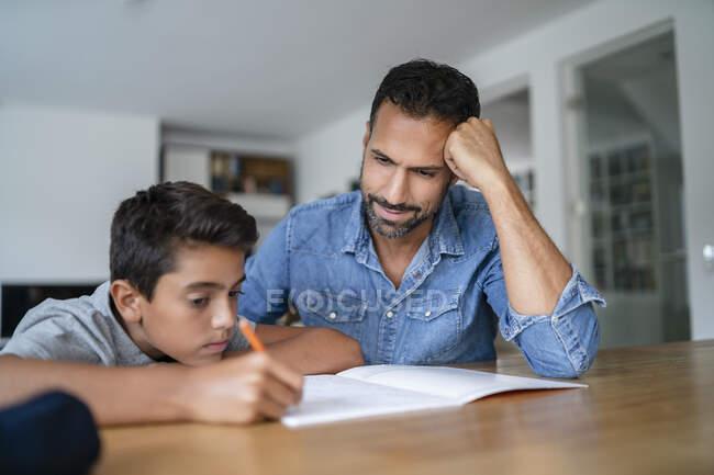 Батько допомагає синові робити домашнє завдання. — стокове фото