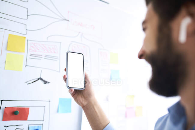 Businessman standing in front of a whiteboard and holding aloft his smartphone — Stock Photo