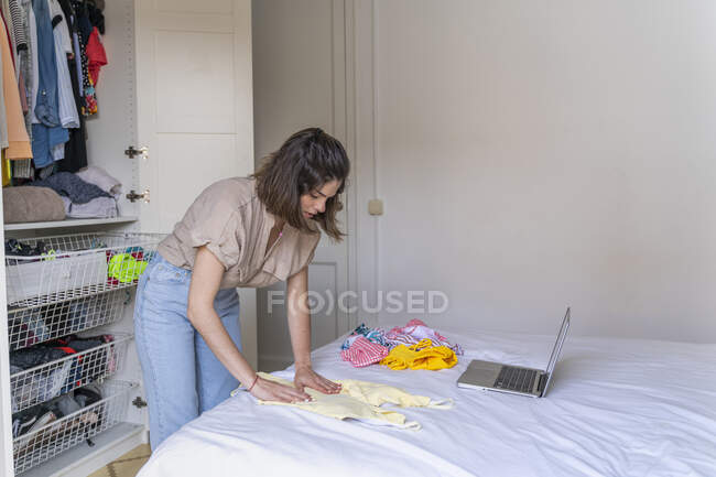 Young woman with laptop placing clothes on bed — Stock Photo