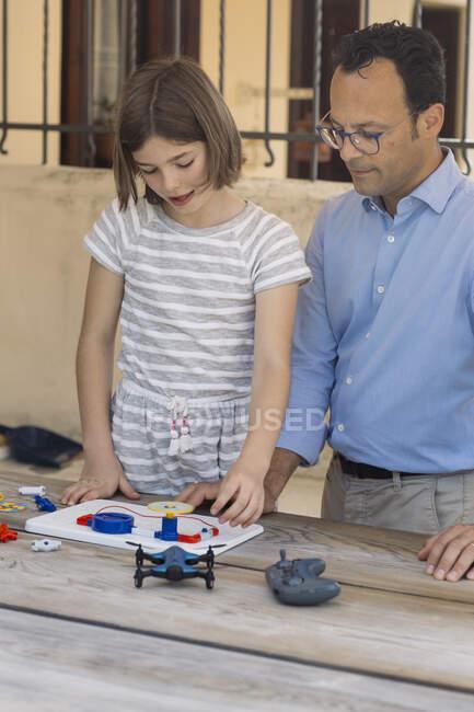 Padre enseñando a su hija electrónica y robótica - foto de stock