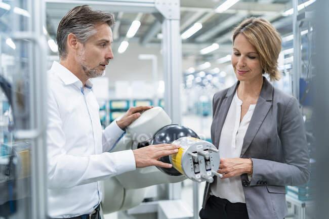 Mujer de negocios y hombre hablando en el robot de montaje en una fábrica - foto de stock