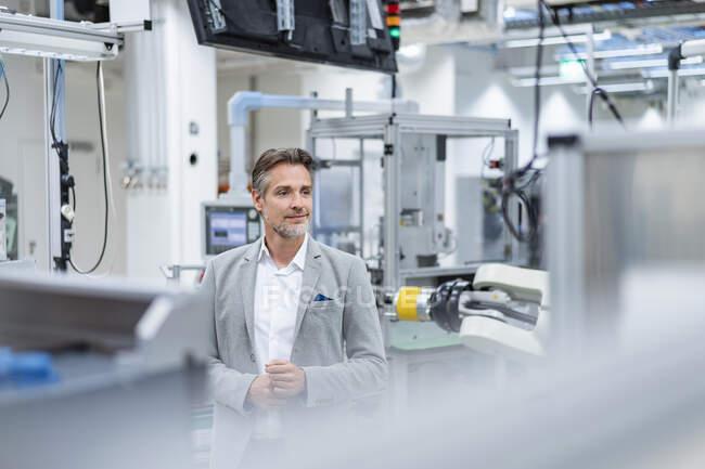 Retrato de un empresario confiado en una fábrica moderna - foto de stock