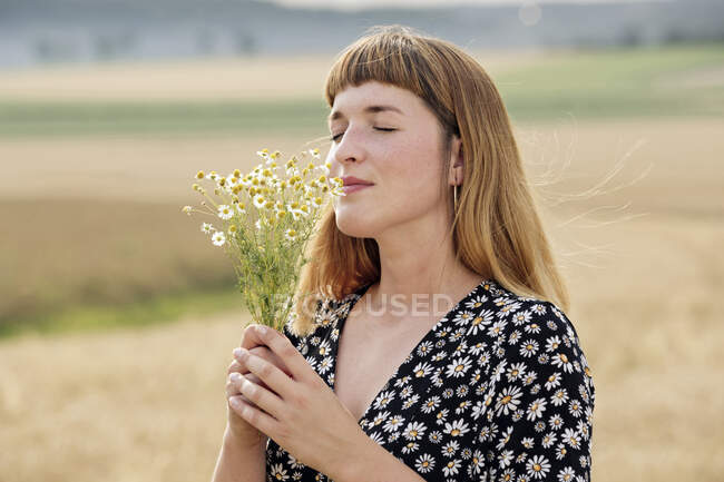 Smiling young woman with eyes closed smelling bunch of chamomile flower in nature — Stock Photo