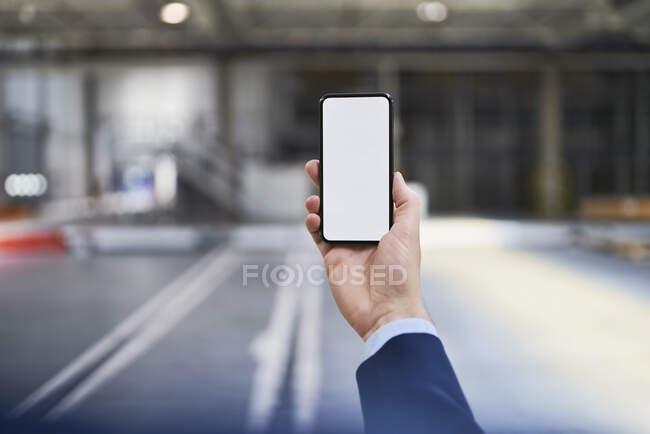 Крупный план предпринимателя, держащего мобильный телефон на заводе — стоковое фото